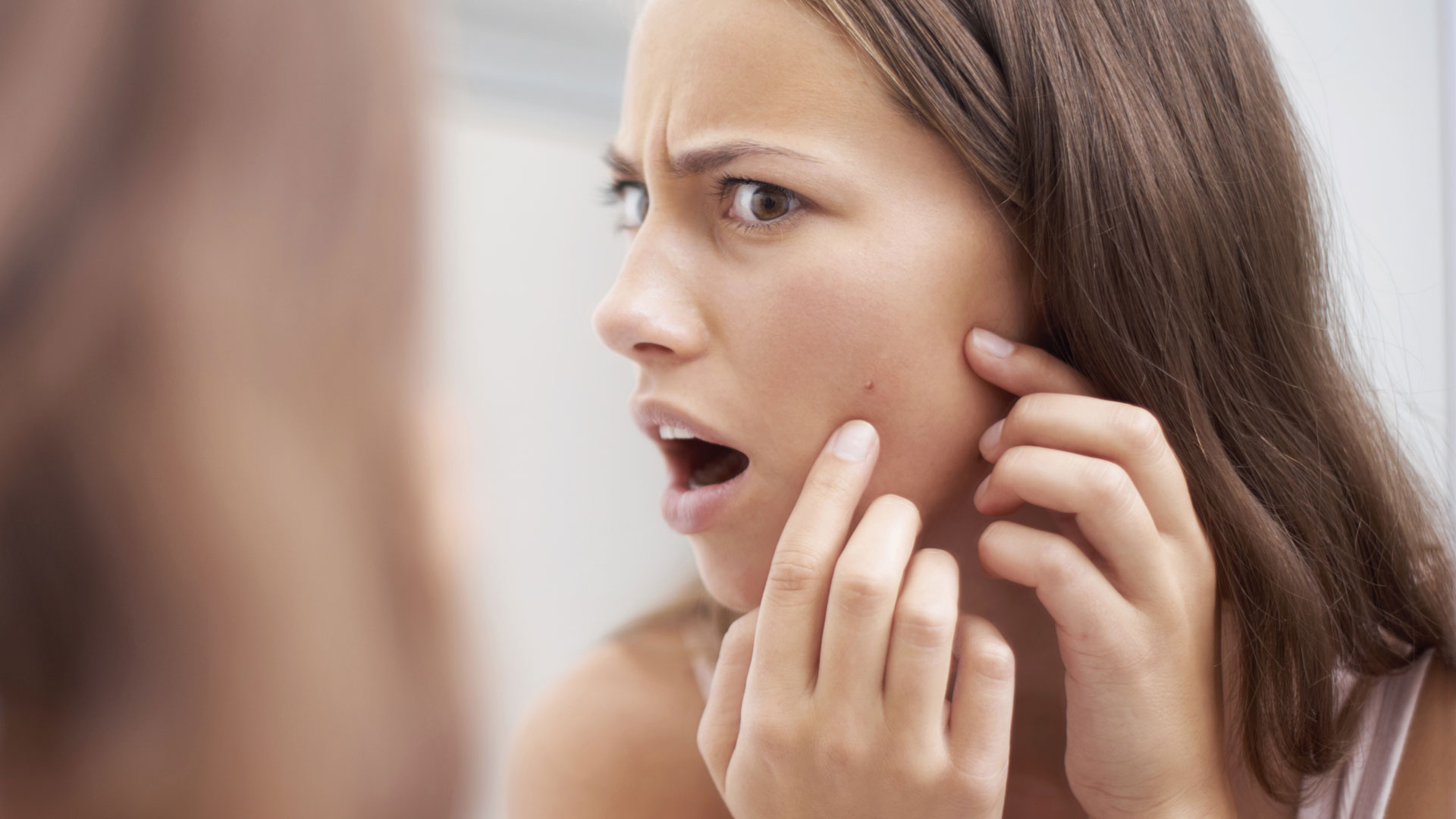 Woman surprised by blemishes on face