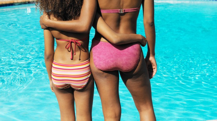 mother and daughter beside swimming-pool facing
