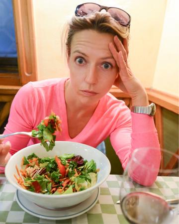 Bored woman eating salad