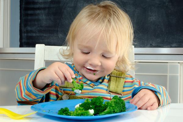 Boy eating broccoli