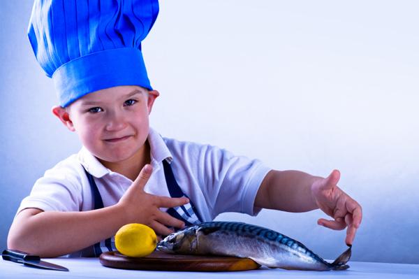 Boy preparing fish for dinner
