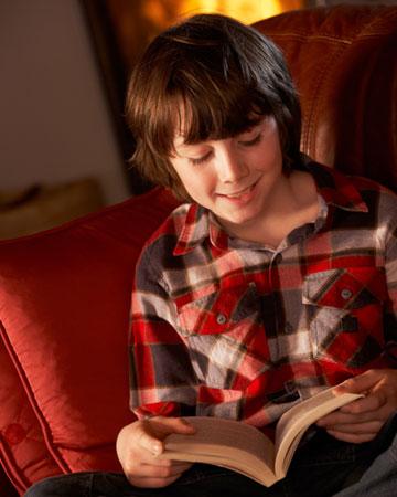 Boy reading by fire