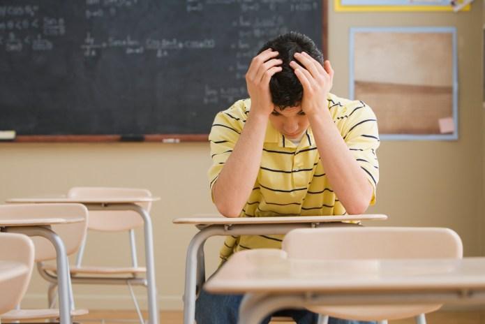 Frustrated Teenage Boy in Classroom