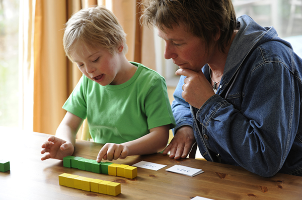 Boy with down syndrome working with his teacher | Sheknows.com