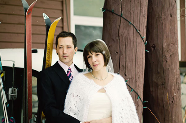 Bride and groom standing in front of skis | Sheknows.ca