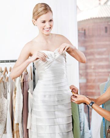 Bride having dress fitting
