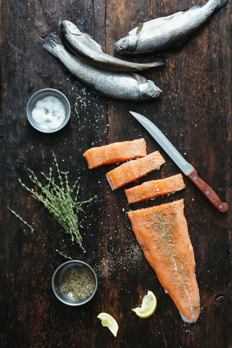Salmon cut up and whole with herbs on table.