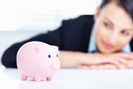 Business woman looking at piggy bank on her desk