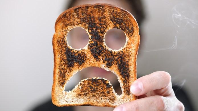 Man holding up a burnt slice