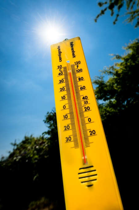 Yellow thermometer against blue sky with sun