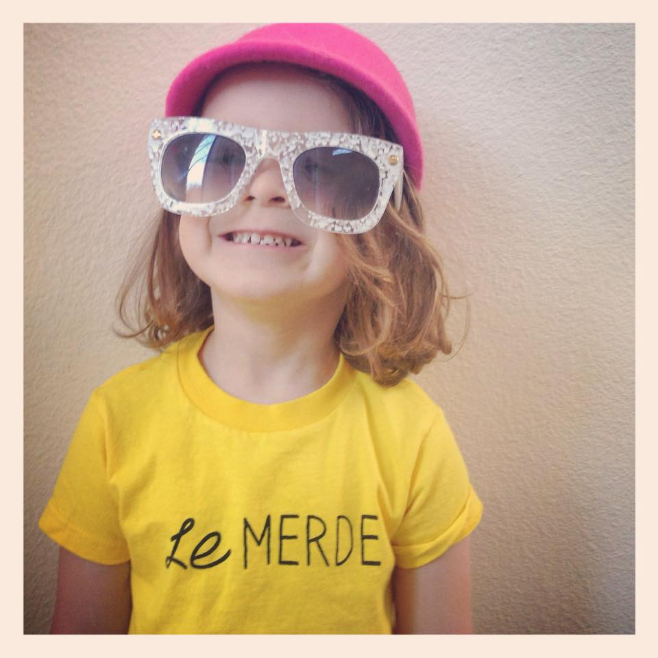 Child Wearing Hat, Sunglasses, and Yellow Shirt from Le Merde Seattle