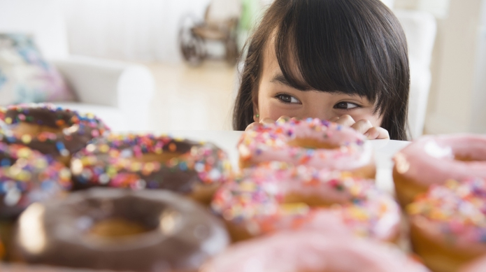 Filipino girl peering at donuts on