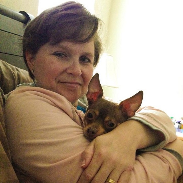 woman cuddling chihuahua