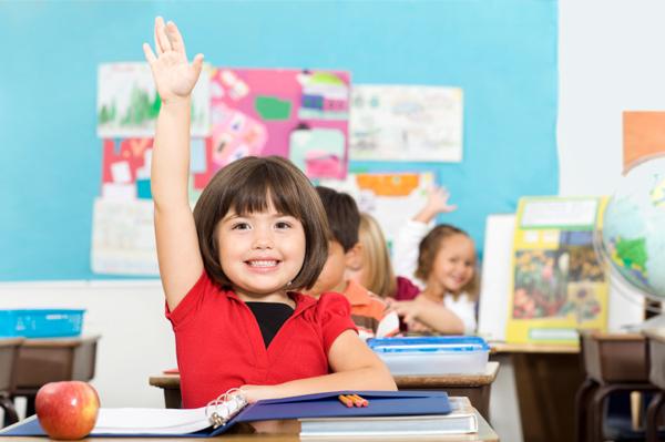 Child raising hand in class