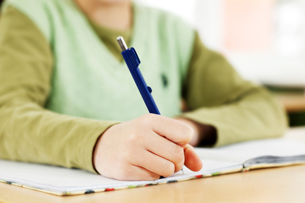 Child writing in notebook at school | Sheknows.com
