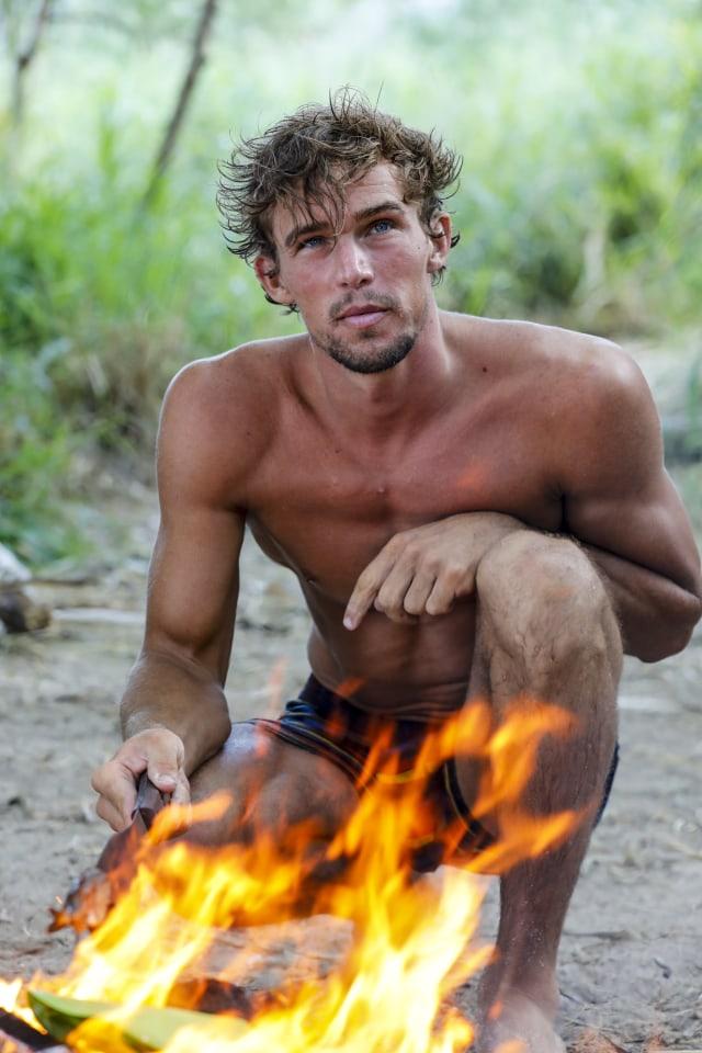 Cole Medders sits by fire on Survivor: Heroes Vs. Healers Vs. Hustlers