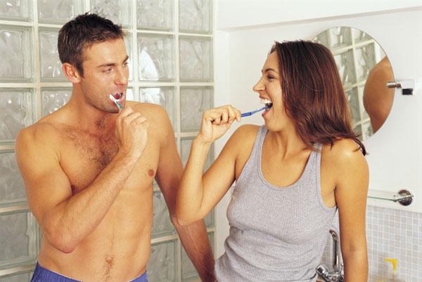 In the bathroom couple brushing teeth
