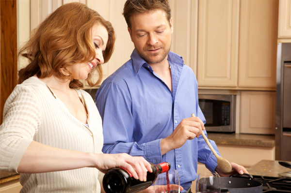 Couple drinking wine and cooking dinner