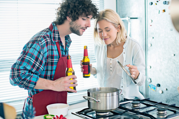 Couple cooking with beer