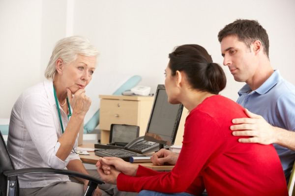 Couple discussing fertility treatments with doctor