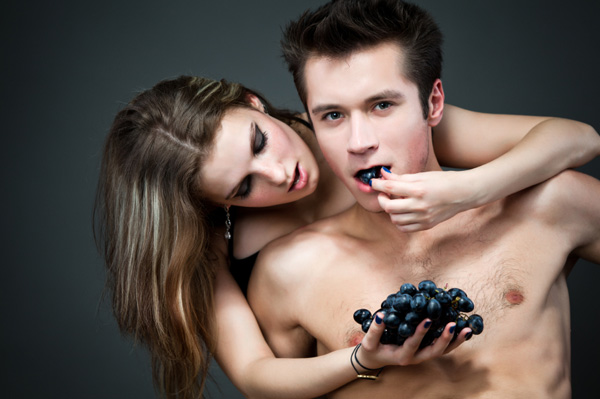 Sexy couple eating grapes