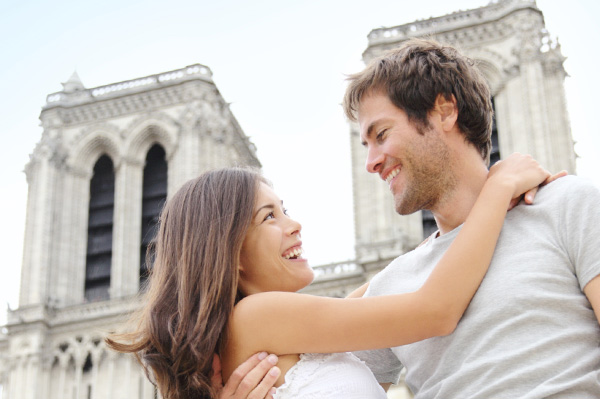 Couple hugging in front of Notre Dame while traveling