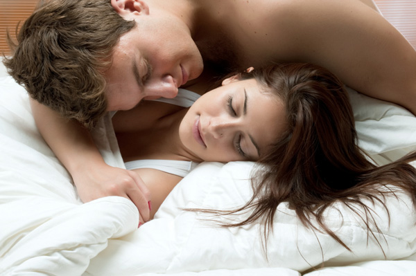 Couple in covers in bed