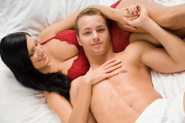 Happy couple lying in bed.