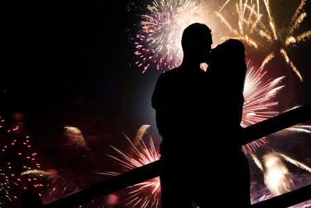 Couple kissing in front of fireworks