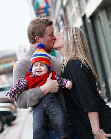 Couple kissing in front of baby