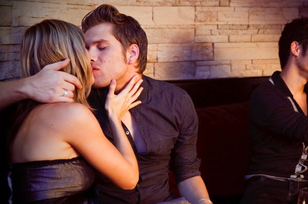 Couple making out at bar