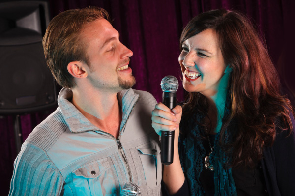 https://www.sheknows.com/wp-content/uploads/2018/08/couple-performing-karaoke_x0loda.jpeg