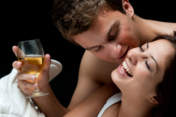 Couple in bed with wine