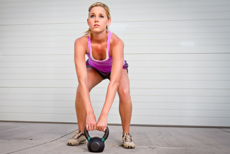 woman lifting kettlebell in crossfit class