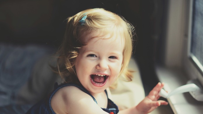 Little blonde girl laughing.