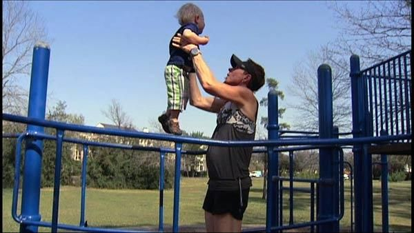 Dad doing playground exercises with toddler