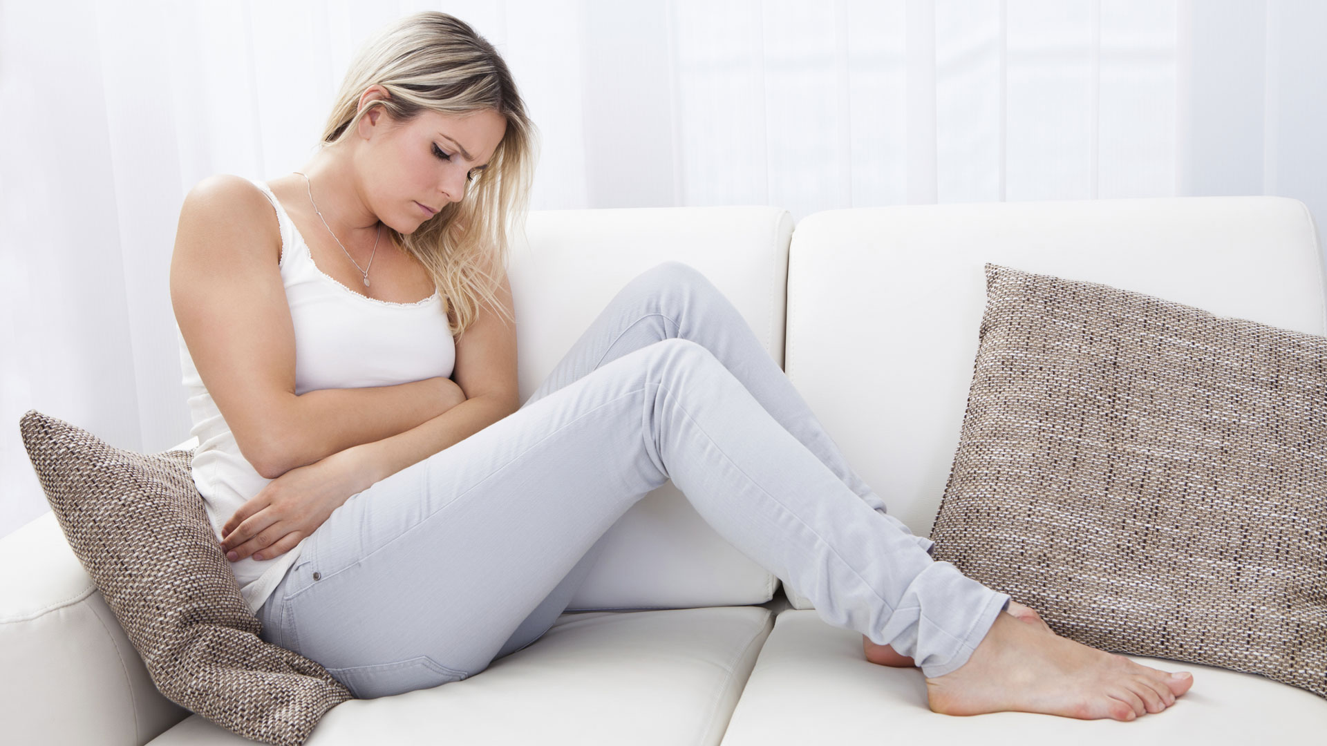 Woman holding stomach from digestive issues