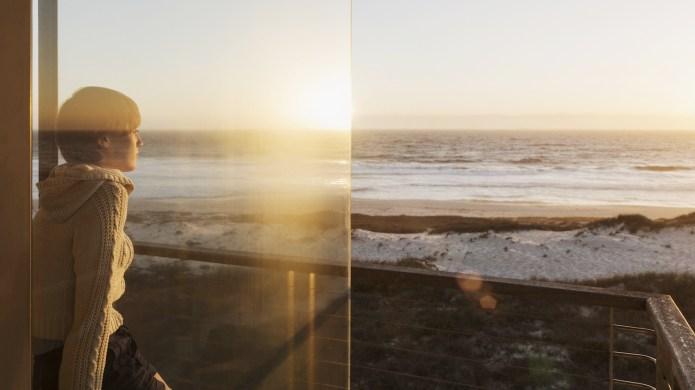 Woman watching sunset over ocean