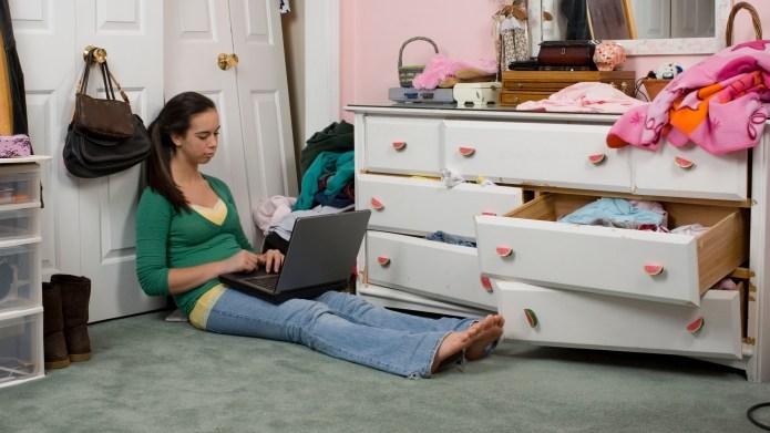 Teenage girl using laptop in messy