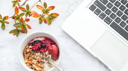 Laptop and breakfast bowl on table
