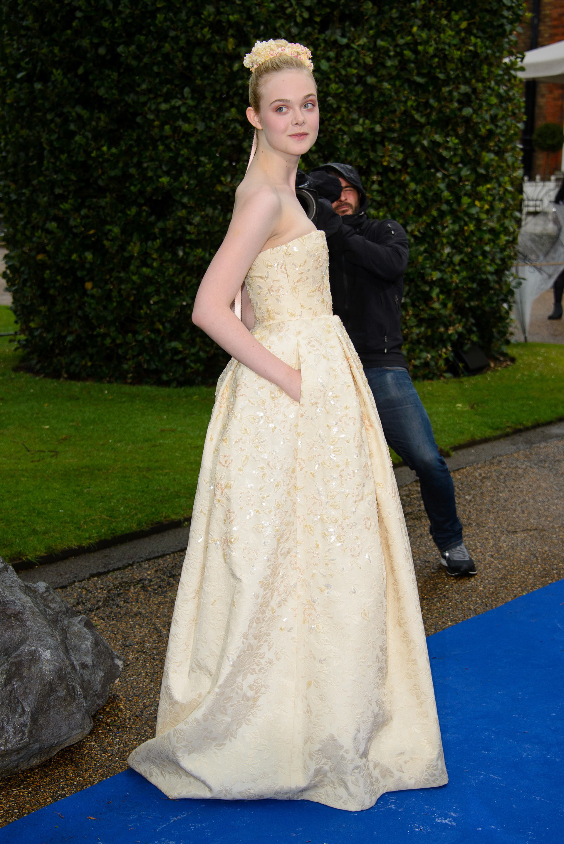 Elle Fanning wearing embroidered strapless gown at a Maleficent promo event