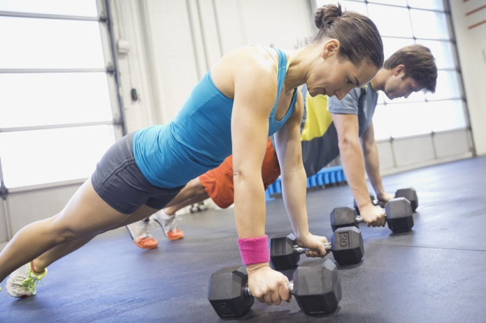 Athletes practicing dumbbell pushup rows