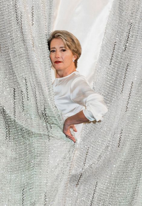 Emma Thompson in white posing behind curtains