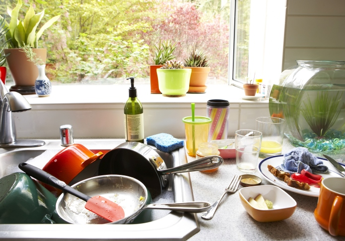 Dirty dishes piled in kitchen sink,