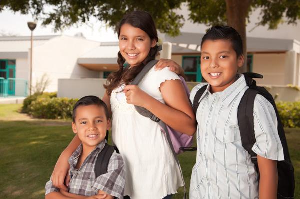 Three children in front of school