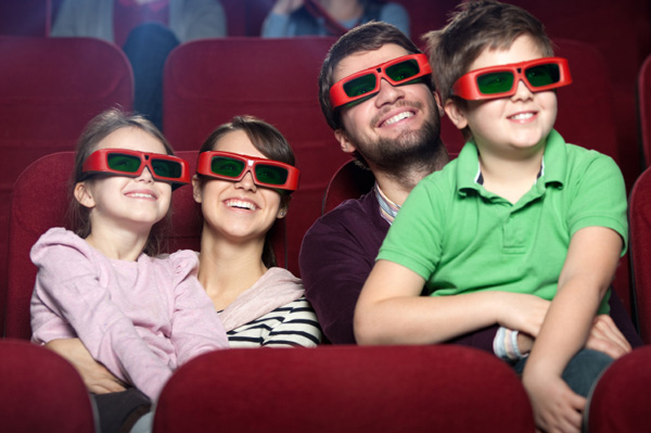 Family of four in a movie theater smiling