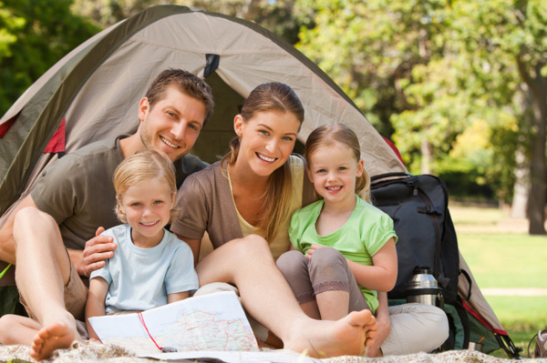 Family camping and smiling in front of tent