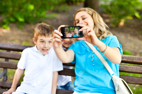 Mother and son taking photos together using smartphone