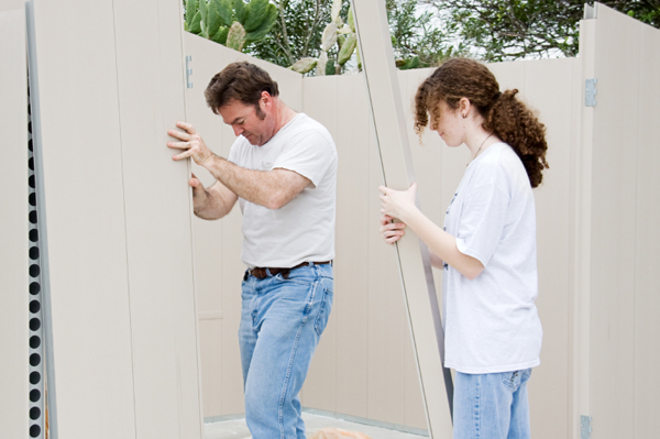 Father and daughter volunteering building a house