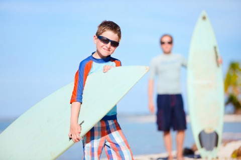 father and son on beach with surfboards